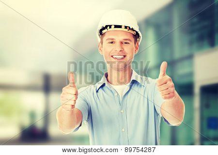 Portrait of a builder in white helmet gesturing OK