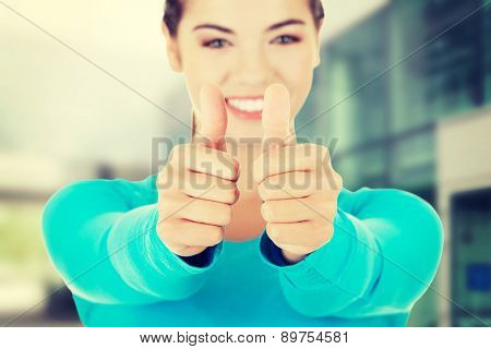 Teen woman in casual clothes gesturing thumbs up