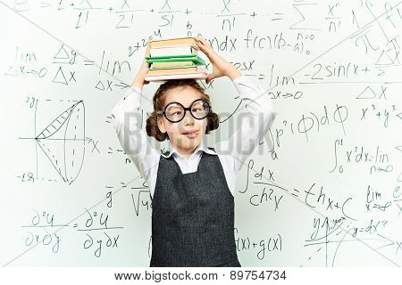 Funny smart schoolgirl in big glasses stands with books at the blackboard. Education.