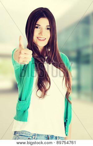 Teen girl gesturing thumbs up.