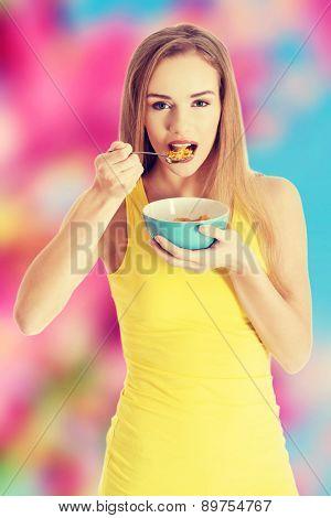 Beautiful blonde woman eating cereal