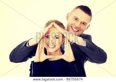 Young smiling businesspeople do sign with their hands