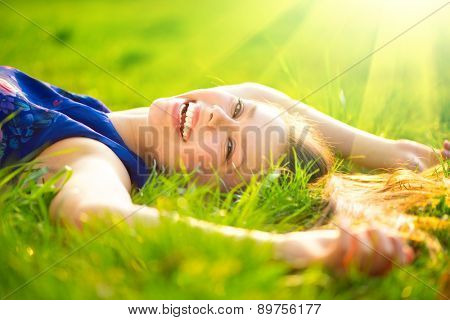 Beautiful Young Woman lying on the field in green grass and laughing. Outdoors. Enjoy Nature. Healthy Smiling Girl on spring lawn