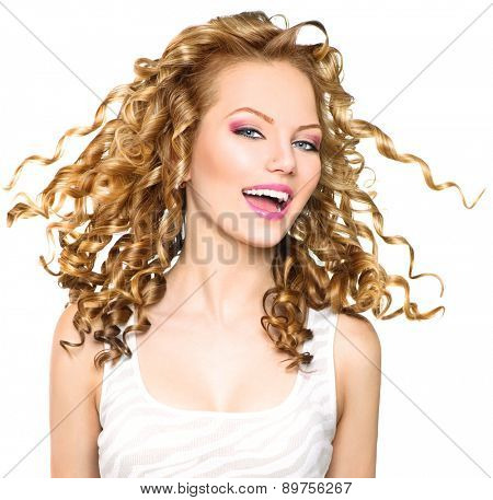 Beauty model girl with blowing Blonde curly hair. Portrait isolated on white background. Healthy wavy hair. Hairstyle. Beautiful smiling young woman. Beautiful face, natural make up. Long permed hair