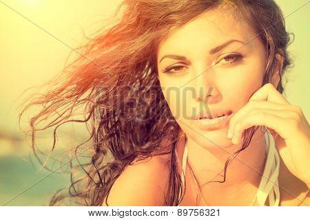Beauty Sunshine Girl Portrait. Beautiful Model Woman over sea. Sunny Summer Day under the Hot Sun on the Beach. Ocean. Sea