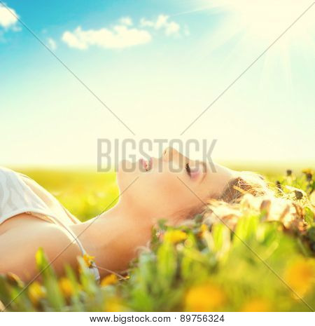 Beautiful Healthy Girl lying on summer field with flowers. Outdoors. Enjoy Nature. Healthy Smiling Girl on spring lawn. Allergy free concept. Freedom. Happy person outdoor
