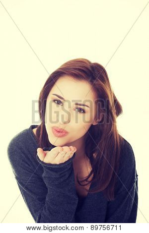 Young beautiful woman blow a kiss