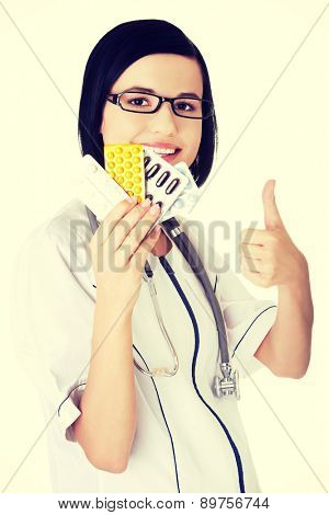 Happy female doctor holding pills