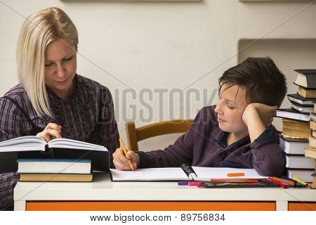 Young student doing homework with a tutor.