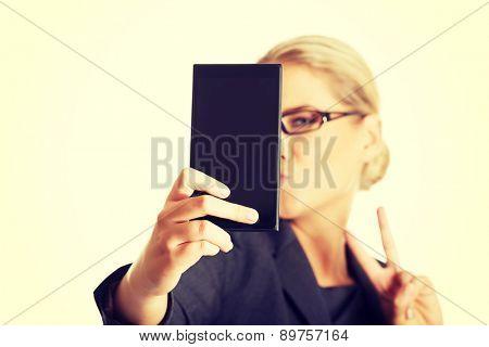 Businesswoman taking selfie with smartphone