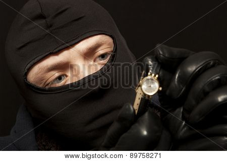 Thief. Man in black mask with a golden watch. Focus on thief