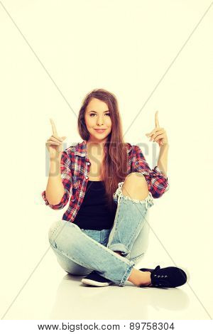 Woman sitting cross-legged and pointing