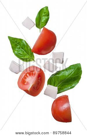 falling red tomatoes, mozzarella and basil isolated on white - caprese, traditional italian ingredients