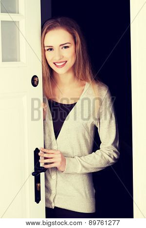 Young woman opening her house door