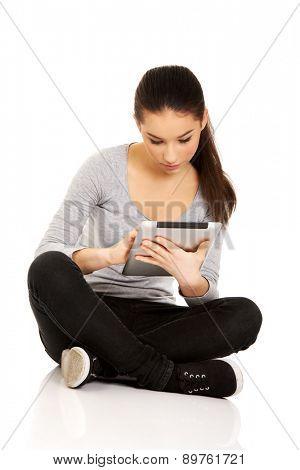 Teenage woman with tablet sitting cross legged.