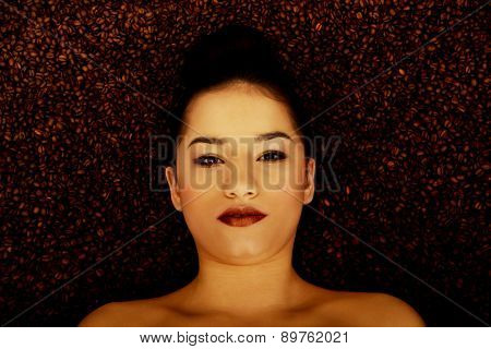 Attractive topless woman lying in coffee grains.