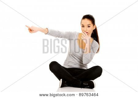 Shocked woman sitting cross legged pointing aside.
