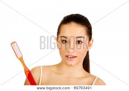 Young shocked woman holding big toothbrush and smiling.