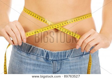 Slim caucasian woman measuring her waist.