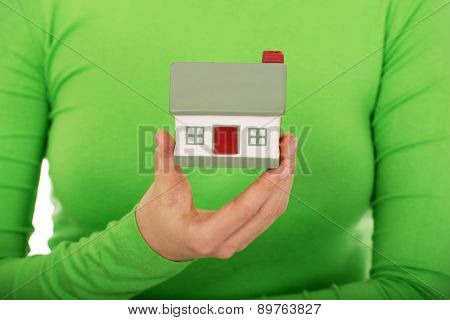 Young woman holding small house.