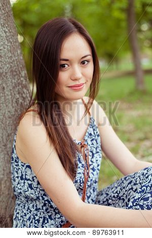 Asian woman resting in summer park outdoor