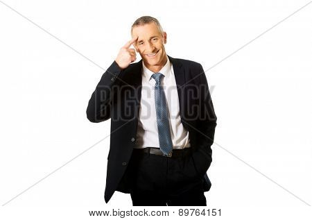 Mature businessman gesturing with finger against temple