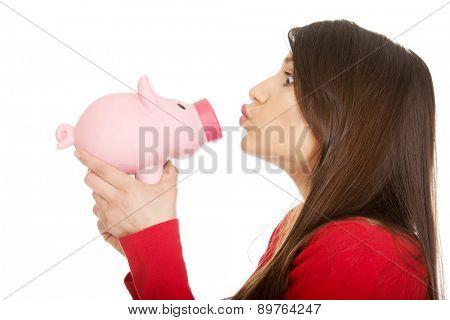 Happy student woman  kissing a piggybank.