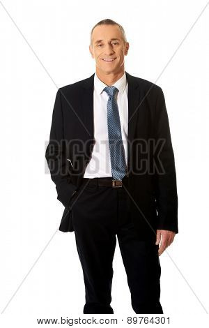 Smiling mature businessman with hand in pocket.