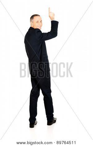 Full length businessman pointing upwards.