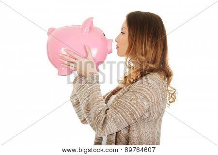 Beautiful casual woman kissing piggy-bank.