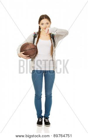 Teenager with basketball and thumbs down.
