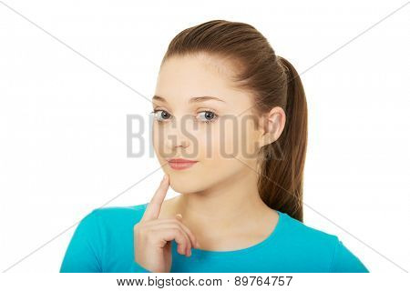 Thoughtful teenage woman touching chin.