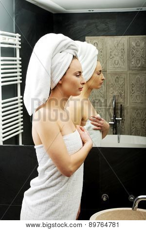 Beautiful woman wrapped in towel at bathroom.