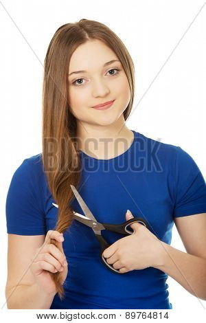 Smiling teenage woman cutting her hair.
