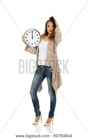 Beautiful shocked woman with clock.