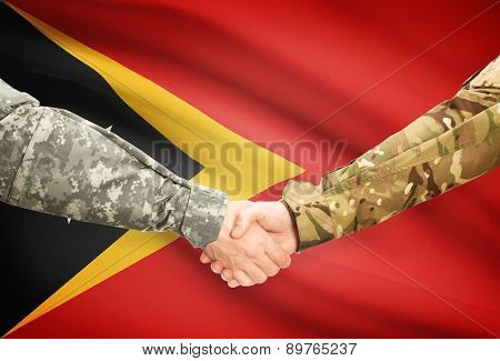 Men In Uniform Shaking Hands With Flag On Background - East Timor