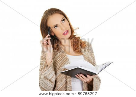 Casual thoughtful woman with notebook.