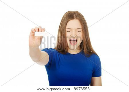 Shocked teenage woman holding pregnancy test.