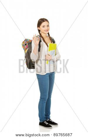 Teenager girl with school backpack and perfect sign.