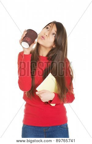 Happy young woman with coffee and notebook.
