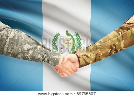Men In Uniform Shaking Hands With Flag On Background - Guatemala