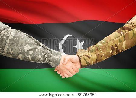 Men In Uniform Shaking Hands With Flag On Background - Libya