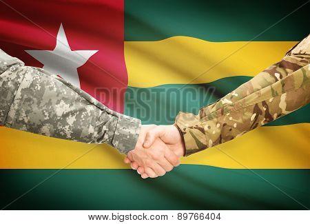 Men In Uniform Shaking Hands With Flag On Background - Togo