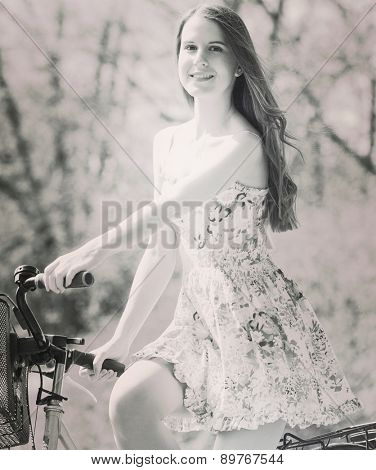 Young woman in short colorful dress with long hair rides a bicycle with  tour summer city park, look and smile to camera. Altered black and whitephoto