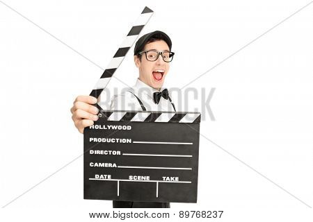 Excited young male movie director posing behind a movie clapperboard isolated on white background
