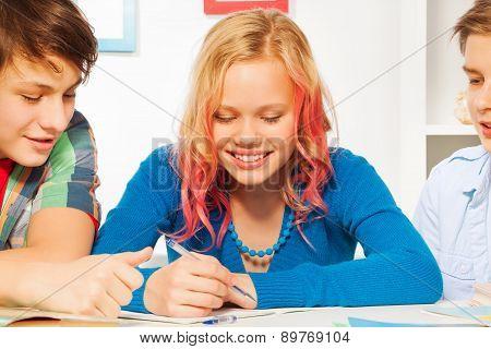 Boys help cute blond teen girl do homework