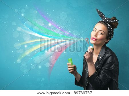 Beautiful girl blowing abstract colorful bubbles and lines on blue background