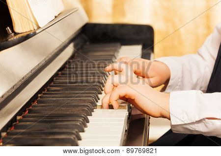 Child's hands playing on the piano-keys