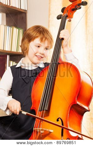 Happy girl in school uniform playing on the cello