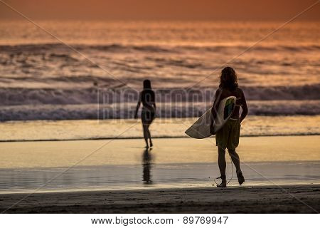 Surfer On The Beach At Sunset Tme
